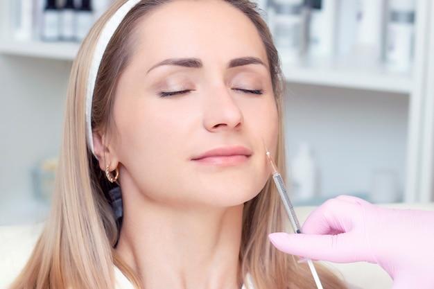 Młoda kobieta otrzymująca zastrzyk kosmetyczny botoksu, z bliska. kobieta w salonie piękności. klinika chirurgii plastycznej.