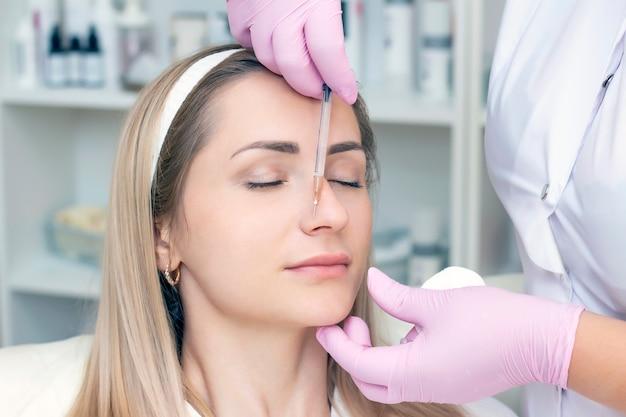 Młoda kobieta otrzymująca zastrzyk kosmetyczny botoksu, z bliska
