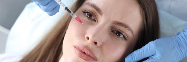 Młoda kobieta otrzymująca zastrzyk przeciwstarzeniowy w klinice urody