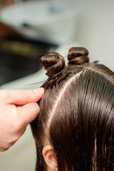 Młoda kobieta otrzymuje proces fryzury przez fryzjera w salonie kosmetycznym