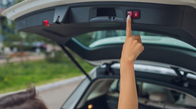 Młoda kobieta otwiera bagażnik samochodu