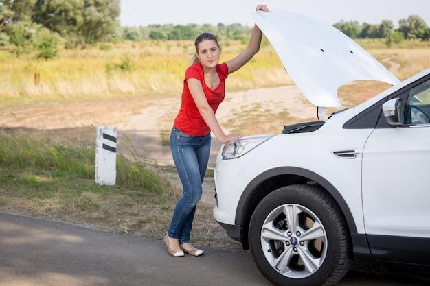 Młoda kobieta otwiera maskę zepsutego samochodu na poboczu drogi