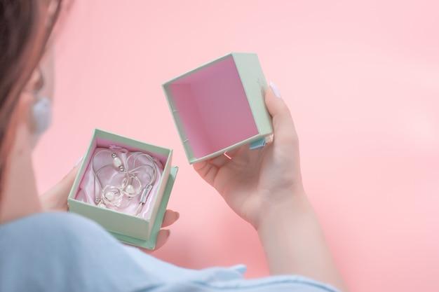 Młoda kobieta otwiera prezent biżuterii, w pudełku ze srebrną biżuterią