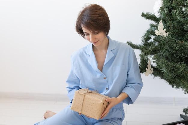 Młoda kobieta otwiera prezenty pod choinką koncepcja bożego narodzenia i nowego roku