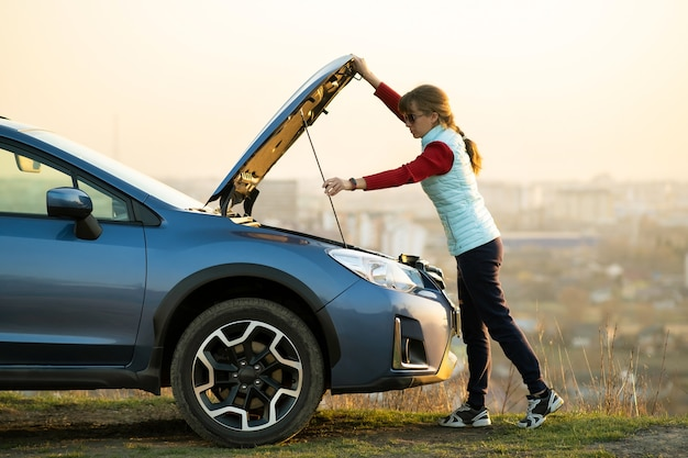 Młoda kobieta otwierając maskę zepsutego samochodu ma problemy z jej pojazdem. kobieta kierowca stojący w pobliżu auto z podniesionym kapturem.