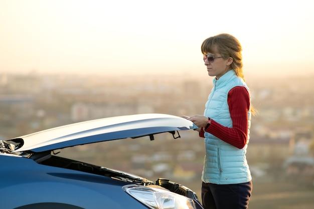 Młoda kobieta otwierając maskę zepsutego samochodu ma problemy z jej pojazdem. kobieta kierowca w pobliżu auto z podniesionym kapturem.