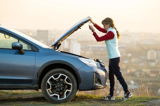 Młoda kobieta otwierając maskę zepsutego samochodu ma problemy z jej pojazdem.