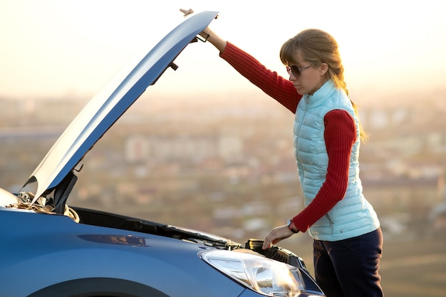 Młoda kobieta, otwierając maskę zepsutego samochodu, ma problemy ze swoim pojazdem. kobieta kierowca w pobliżu samochodu z wyskakującym kapturem.