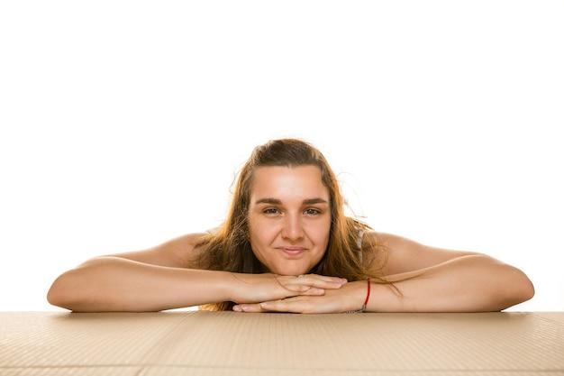 Młoda kobieta, otwierając największą paczkę pocztową na białym tle