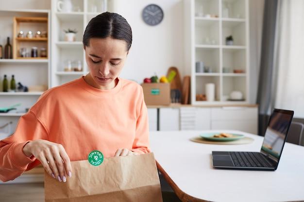 Młoda kobieta, otwierając papierowy pakiet i patrząc jej paczkę, siedząc przy stole przed laptopem