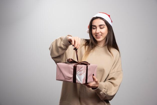 Młoda kobieta, otwierając pudełko prezentów bożonarodzeniowych.