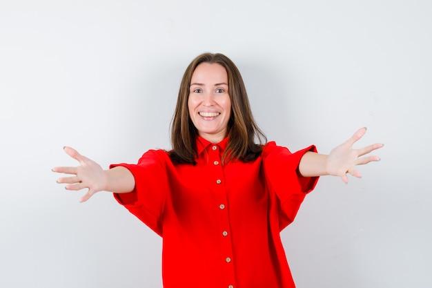 Młoda kobieta otwierając ramiona do uścisku w czerwonej bluzce i patrząc wesoło, widok z przodu.