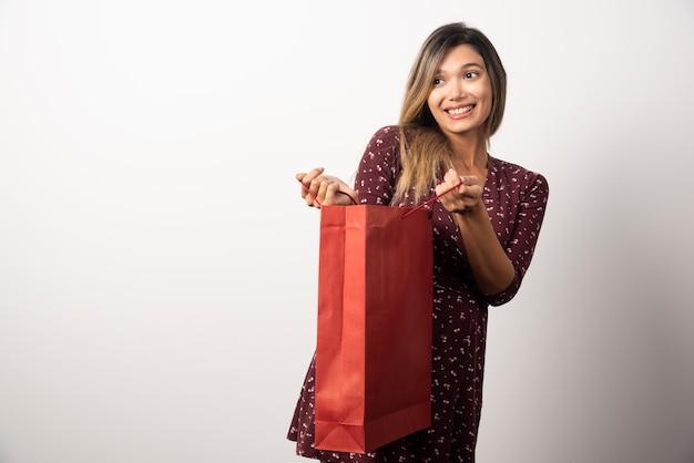 Młoda kobieta, otwierając torbę na zakupy na białej ścianie.