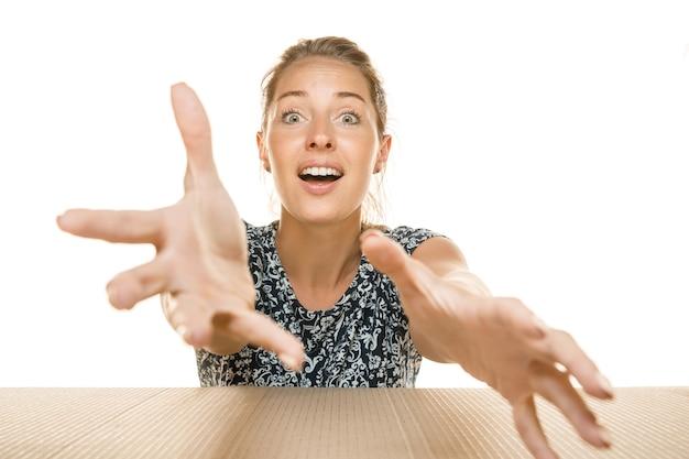 Młoda kobieta otwierająca największą paczkę pocztową na białym tle