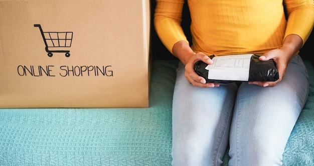 Młoda kobieta otwierająca papierowe pudełko - dziewczyna kupiła produkty online podczas izolacji quaratine