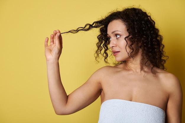 Młoda kobieta owinięta ręcznikiem kąpielowym, trzymająca kosmyk kręconych włosów i patrząc na nią, pozująca na żółtym tle z kopią miejsca