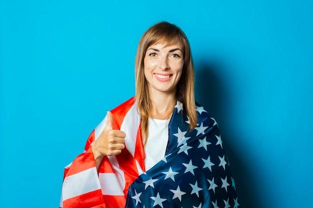 Młoda kobieta owinięta w flagę usa wykonuje gest ręką na niebieskim tle.
