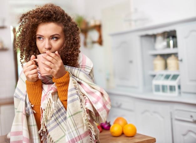 Młoda kobieta owinięta w koc pijąca gorącą herbatę