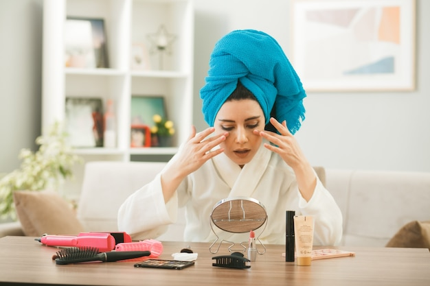 Młoda kobieta owinięta włosami w ręcznik, nakładająca krem tonujący, siedząca przy stole z narzędziami do makijażu w salonie