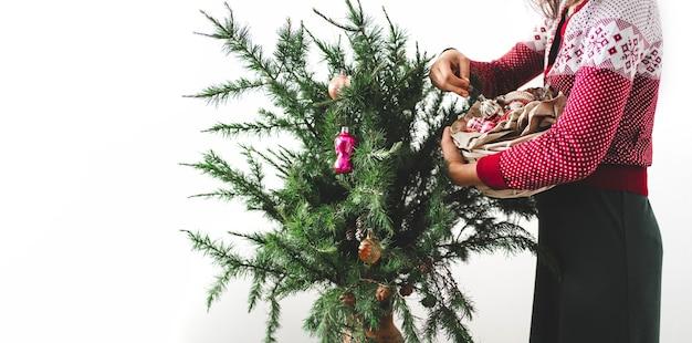 Młoda kobieta ozdabia bombki rocznika choinki. wesołych świąt i wesołych świąt. rano przed bożym narodzeniem. baner z miejsca na kopię.