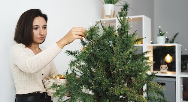 Młoda kobieta ozdabia choinkę. wesołych świąt i wesołych świąt. rano przed bożym narodzeniem.