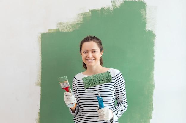 Młoda kobieta paiting ściany wnętrze z wałkiem i pędzlem