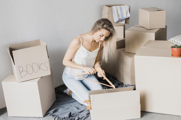 Młoda kobieta pakowania wieszak