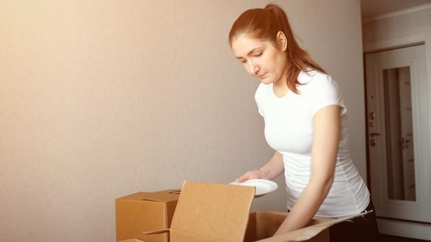Młoda kobieta pakuje naczynia w kartonowe pudełko, światło słoneczne