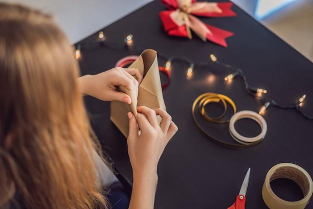 Młoda kobieta pakuje prezenty. prezent zawinięty w papier rzemieślniczy z czerwono-złotą wstążką do