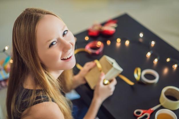Młoda kobieta pakuje prezenty. prezent zawinięty w papier rzemieślniczy z czerwono-złotą wstążką na boże narodzenie