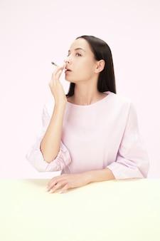 Młoda kobieta palenia papierosów siedząc przy stole w studio. modne kolory. portret kaukaskiej dziewczyny w stylu minimalizmu z miejscem na kopię