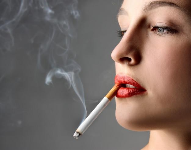 Młoda kobieta pali papierosa