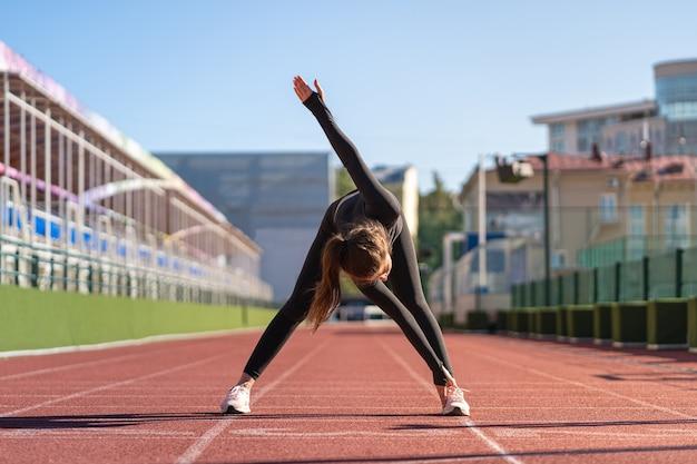 Młoda kobieta pasuje w czarnej odzieży sportowej, rozciągając nogi na stadionie gumy bieżni w słoneczny letni dzień