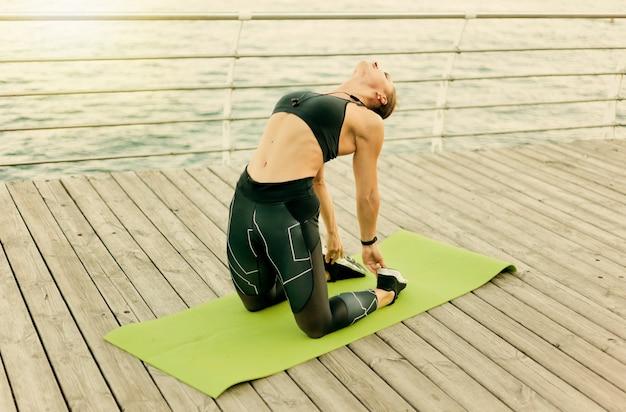 Młoda kobieta pasuje w odzieży sportowej ćwiczeń asan jogi na drewnianym tarasie na plaży nad morzem.