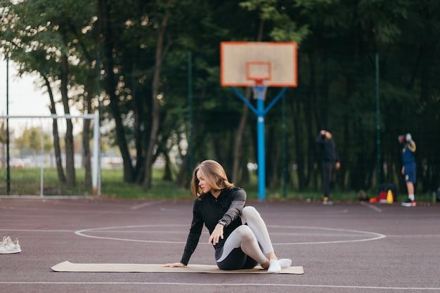 Młoda kobieta pasuje w pociągach odzieży sportowej na świeżym powietrzu na placu zabaw.