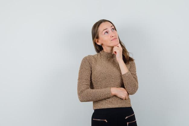 Młoda kobieta, patrząc daleko w złotą bluzkę i zamyślony