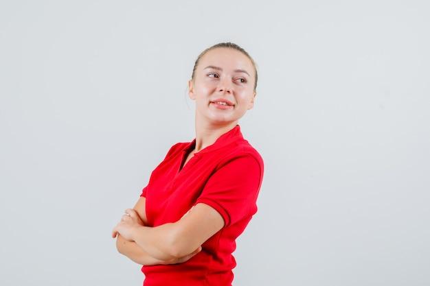 Młoda kobieta, patrząc daleko ze skrzyżowanymi rękami w czerwonej koszulce i patrząc wesoło