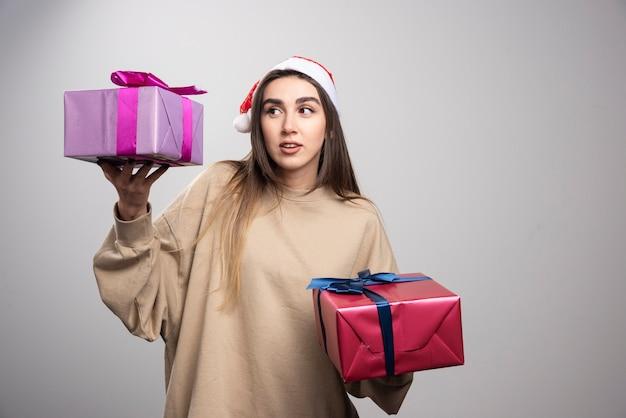 Młoda kobieta, patrząc na dwa pudełka prezentów świątecznych.