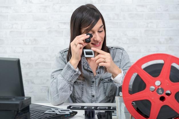 Młoda kobieta, patrząc na film slajdów z lupą