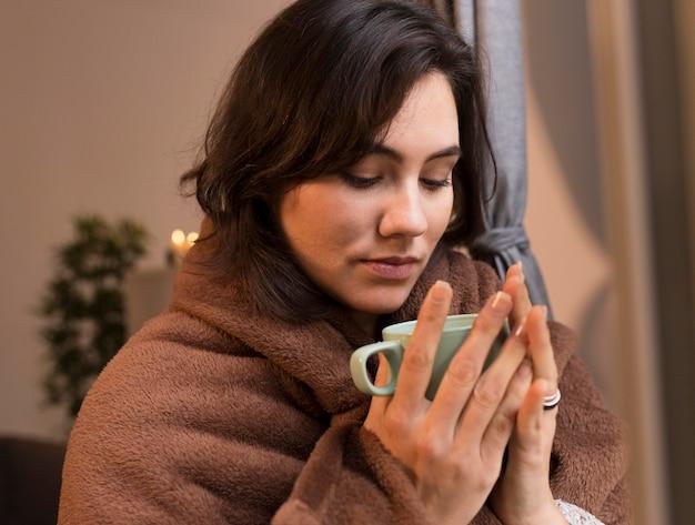 Młoda kobieta, patrząc na jej filiżankę kawy