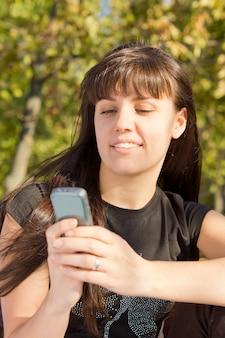 Młoda kobieta, patrząc na jej telefon komórkowy i sms-y.