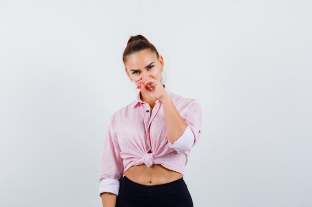 Młoda kobieta patrząc na kamery, trzymając rękę w pobliżu ust w koszuli, spodniach i wyglądającej atrakcyjnie