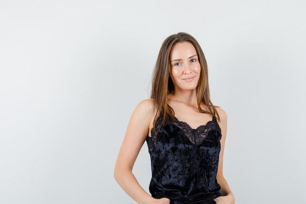 Młoda kobieta patrząc na kamery w czarnym podkoszulku i patrząc pozytywnie