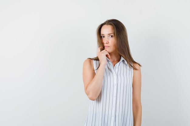 Młoda kobieta patrząc na kamery w t-shirt i patrząc zamyślony, przedni widok.