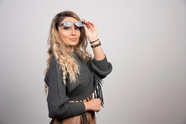 Młoda kobieta patrząc na kamery z okularami.