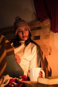 Młoda kobieta, patrząc na kominek w wiejskim otoczeniu z paletą w tyle