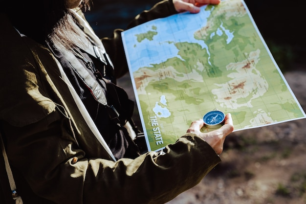 Młoda kobieta, patrząc na mapę i kompas, aby sprawdzić jej pozycję.