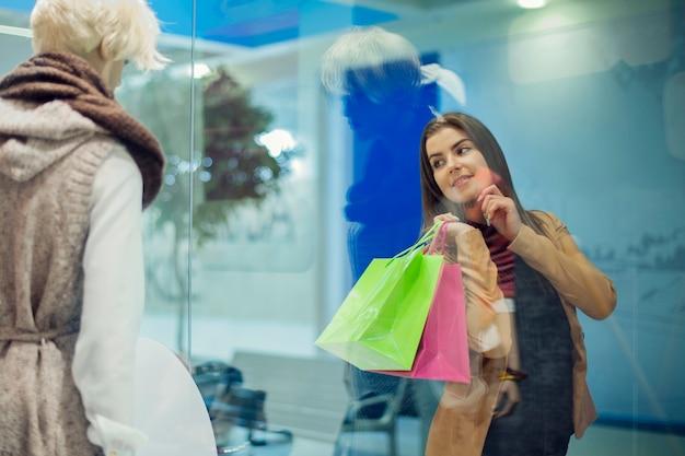 Młoda kobieta, patrząc na okno sklepu