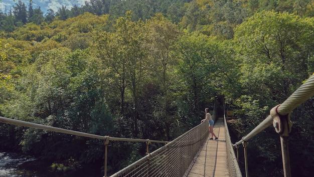 Młoda kobieta patrząc na rzekę z mostu wiszącego w lesie w słoneczny letni dzień. las galicji. droga santiago