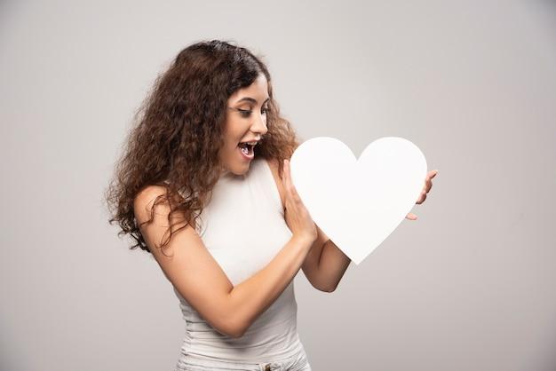 Młoda kobieta, patrząc na serce z białego papieru czerpanego. wysokiej jakości zdjęcie
